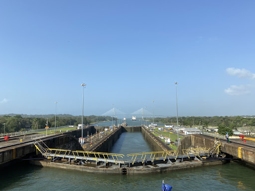 blue skies over placid waters and the locks joining two sides of wooded land