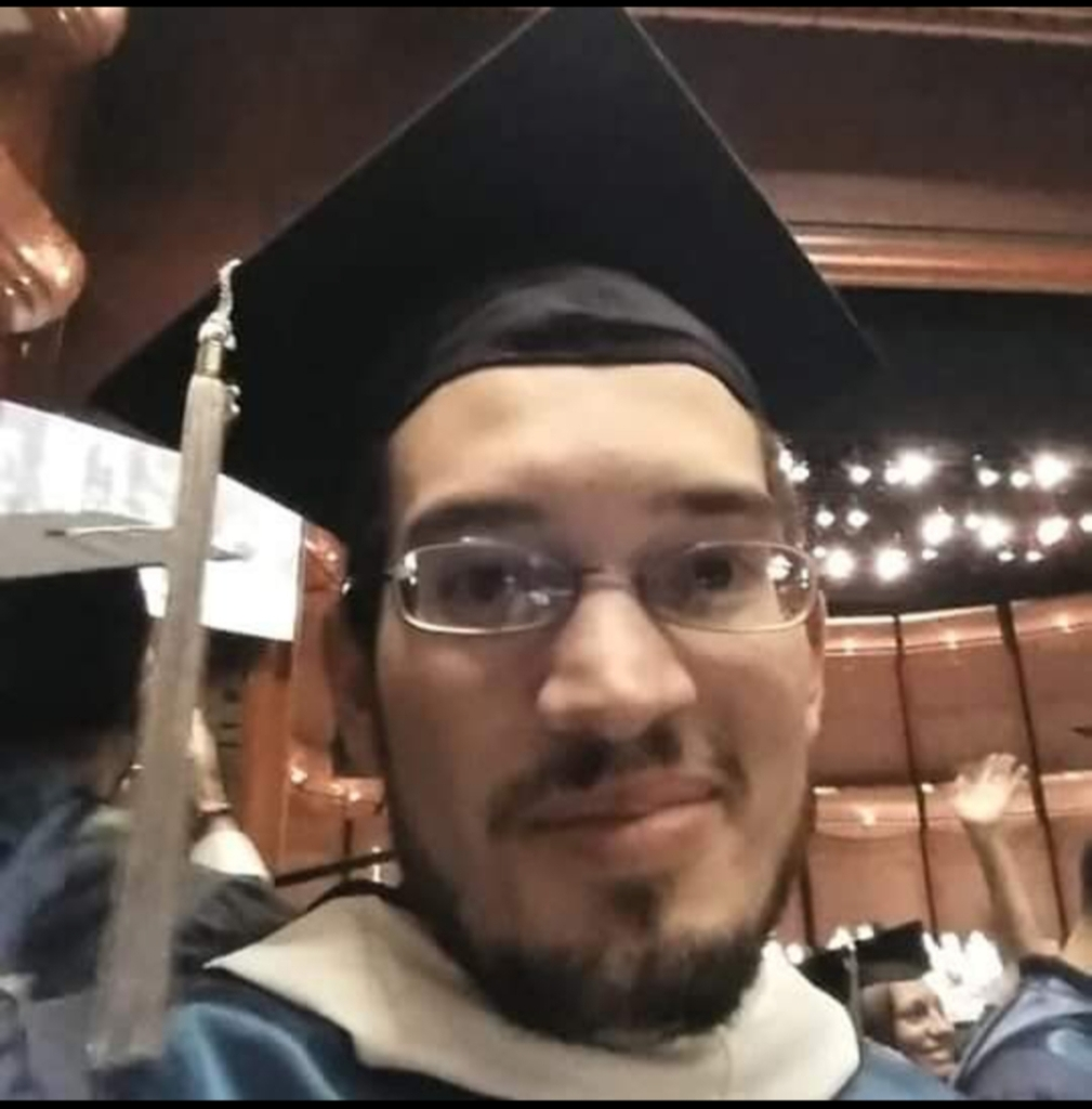 man with glasses and graduating cap