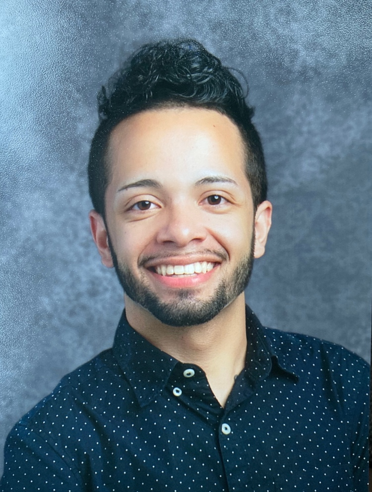 School photo of a smiling Puerto Rican man, a teacher, in a navy blue button down.