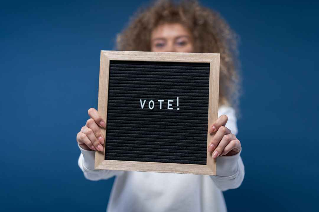 """Woman holding sign saying """"vote"""" atop a blue background"""