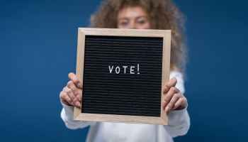 "Woman holding sign saying ""vote"" atop a blue background"
