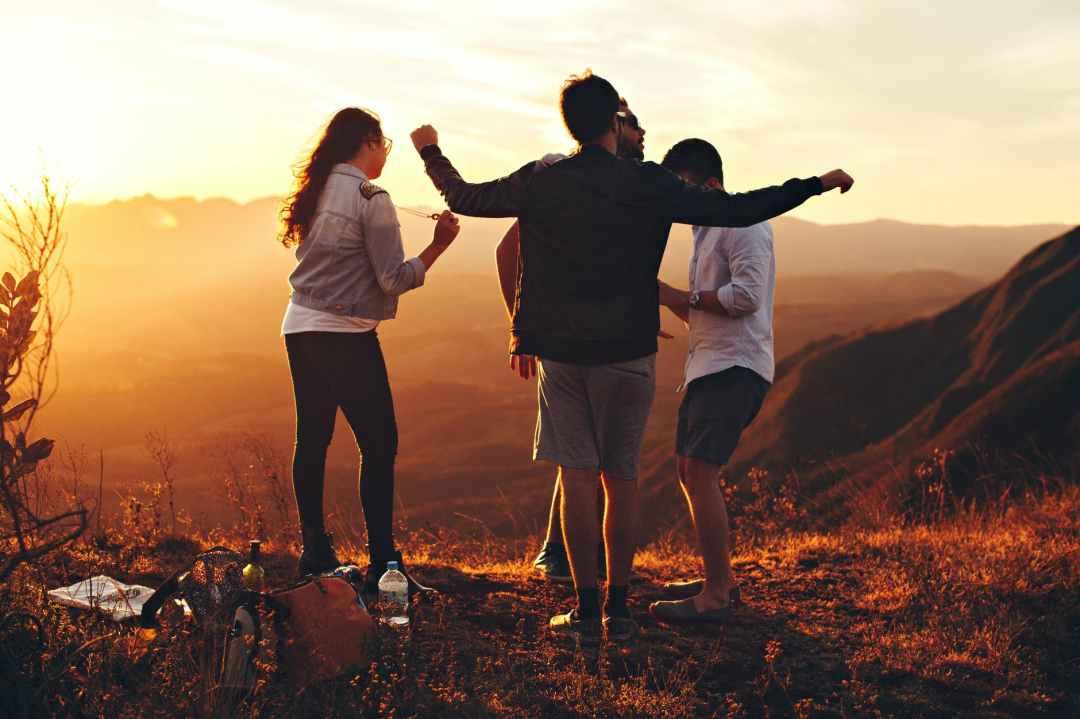 Four carefree teenagers dance in an orange mountain sunset