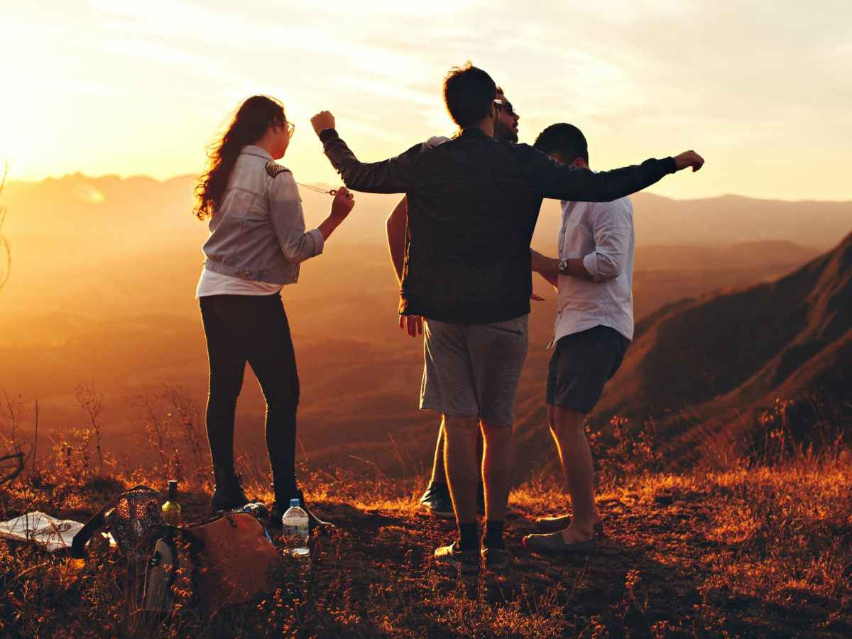 Four carefree teenagers dance in an orange mountain sunset