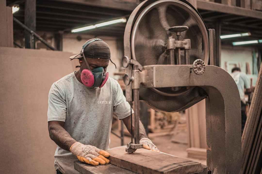 Black man works with wood saw
