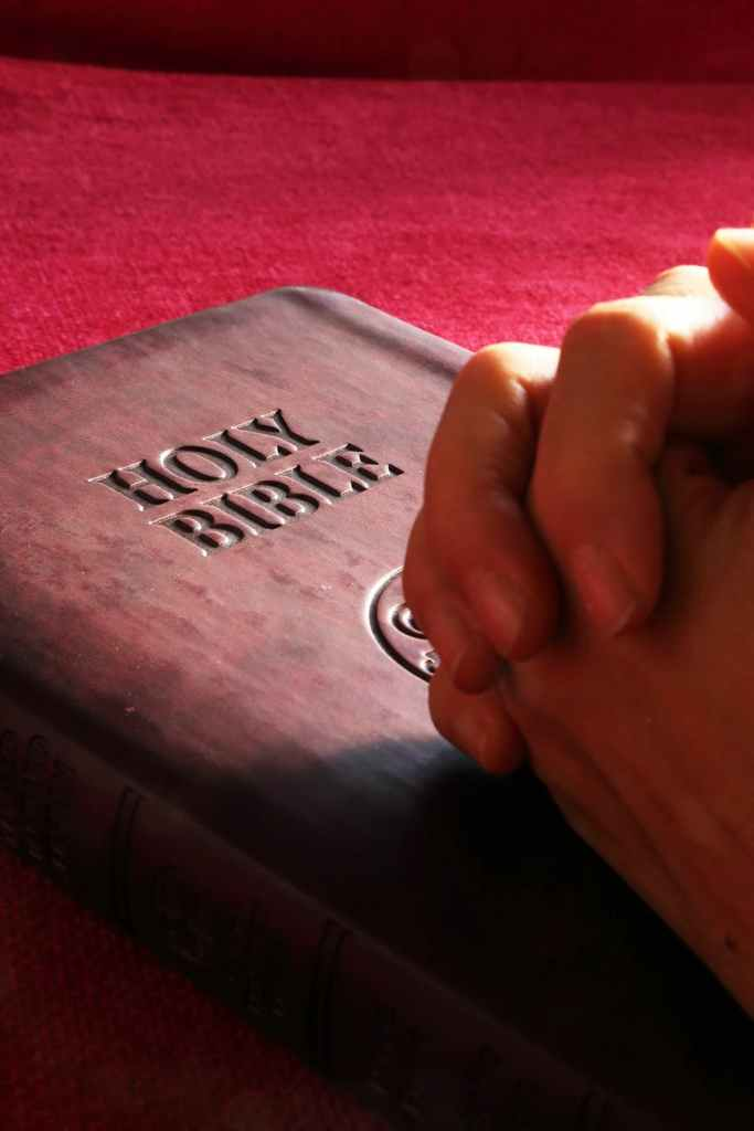 Bible with hands folded