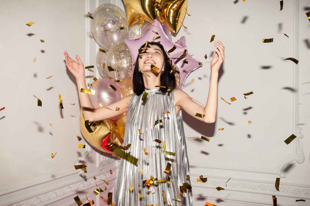 A woman in a silver dress celebrates the New Year with gold confetti