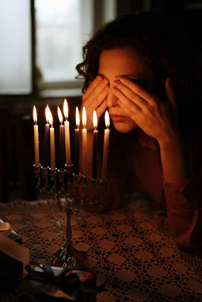 Woman covering her eyes in front of lit candles.