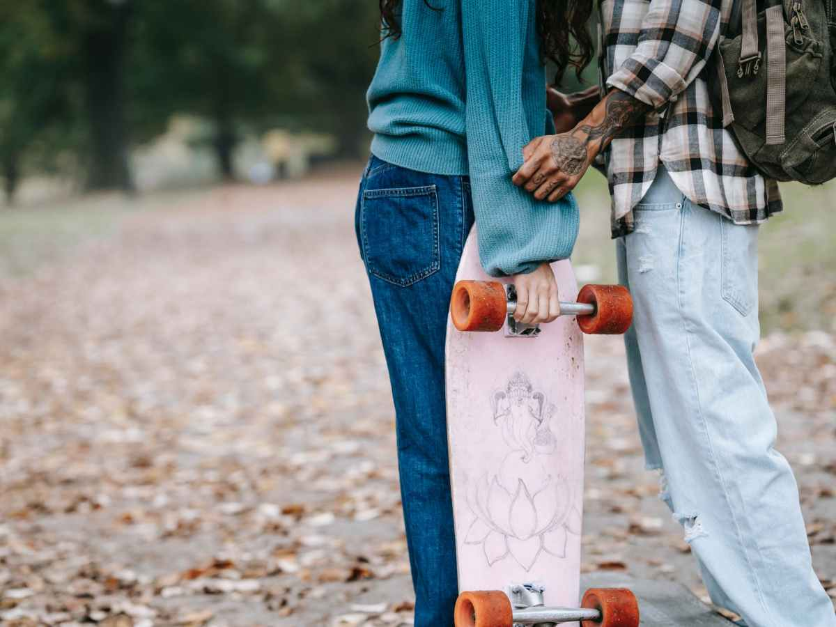 A young couple in jeans with a skateboard. The photo is cropped to show their legs against the autumn backdrop.