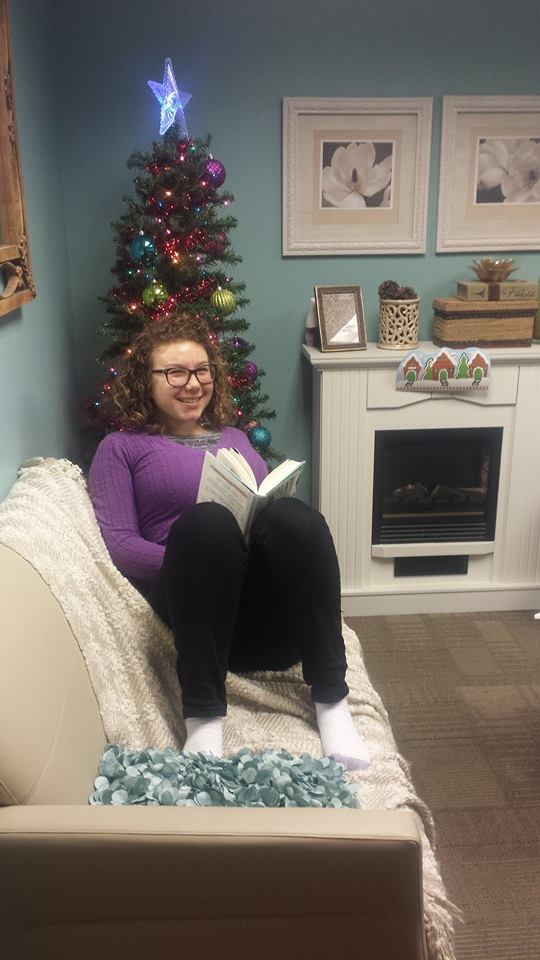 Intersected's Editor-in-chief reading on a couch. Her sweater is purple, and there is a Christmas tree behind her.