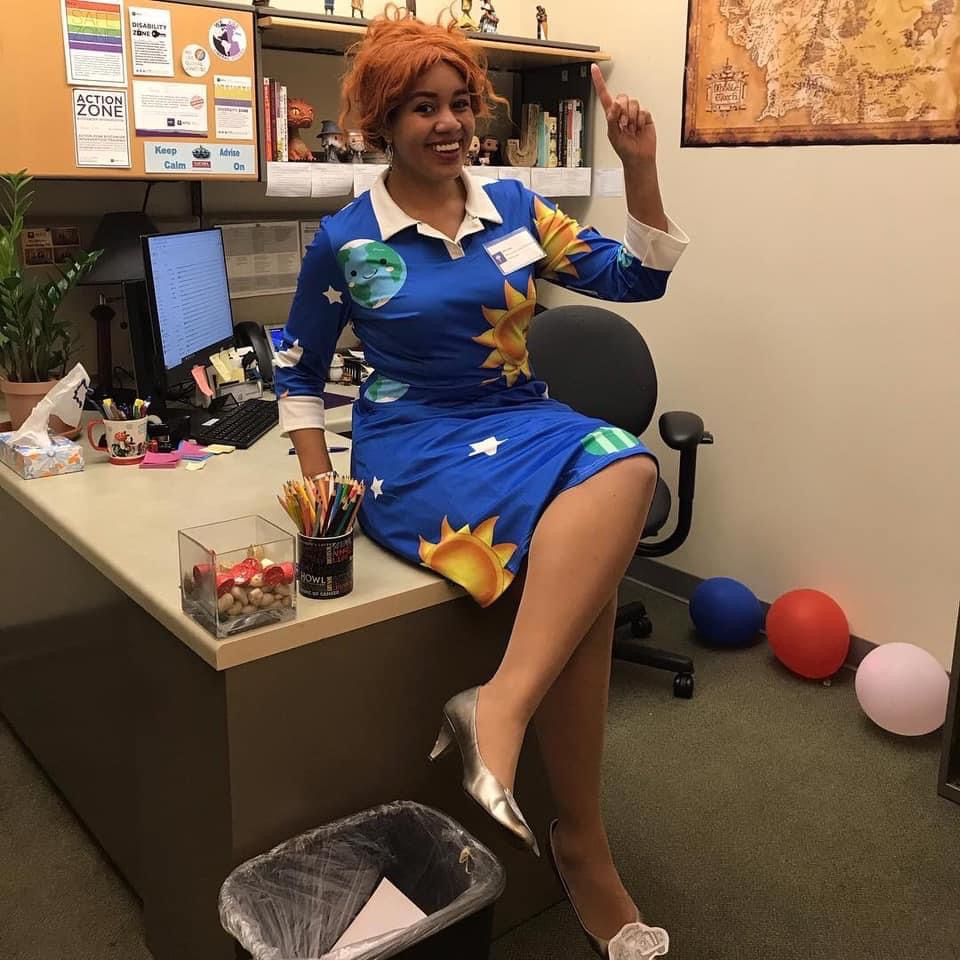 A woman dressed up in silver heels, a patterned blue dress, and red wig to look like Ms. Frizzle. She is sitting on a desk and pointing like she is teaching.