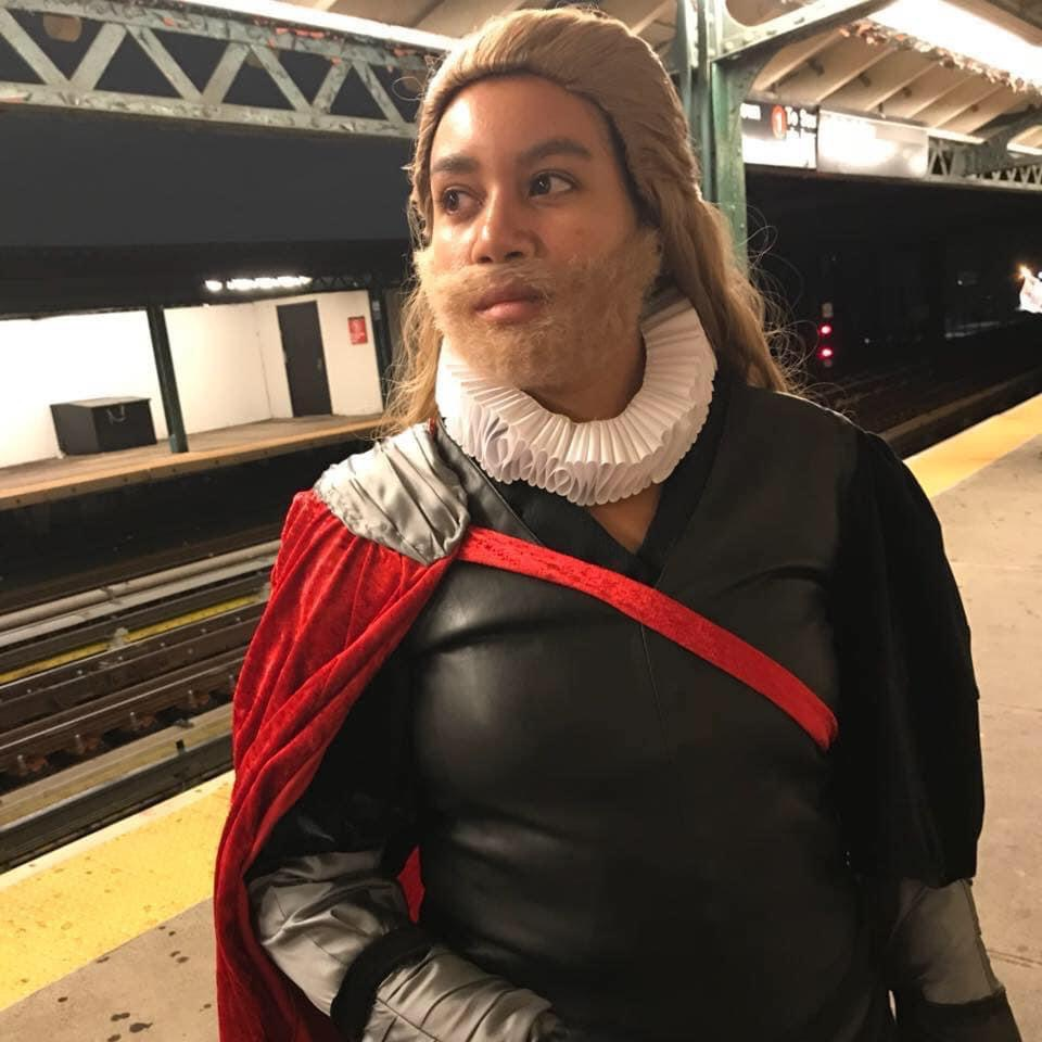 A woman is standing on a train platform dressed in black, with a red cape, white ruffle, and long blonde wig with a matching beard. She is doing cosplay as Shakespearian Thor.
