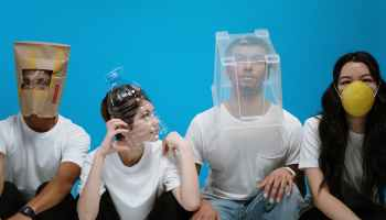 Four young adults in white t-shirts wear funny masks. One has a McDonalds bag, another has a plastic bottle, the third has clear plastic box, and the fourth is wearing a round yellow mask. The wall behind them is blue, and the photo is pleasingly quirky.