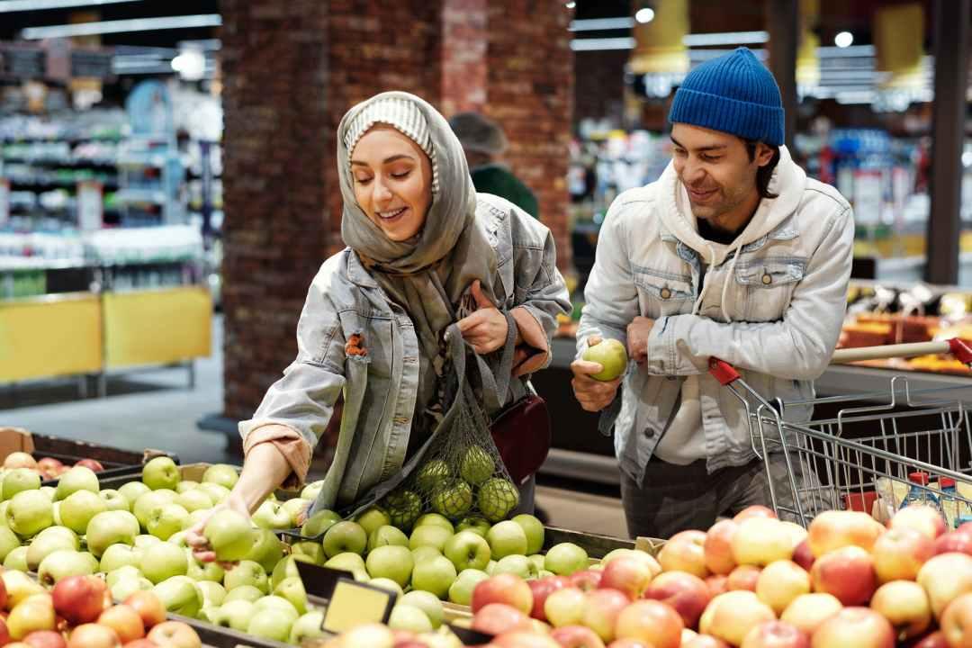 A happy Muslim couple choosing apples from the bin.
