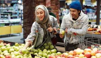 A happy Muslim couple choosing apples from the bin.