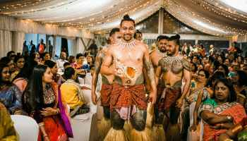 Pacific Islander men walk down an aisle preparing to dance at a wedding. The tent ceiling is lit with twinkly lights, and people in colorful Indian attire fill the rows of cloth white chairs.