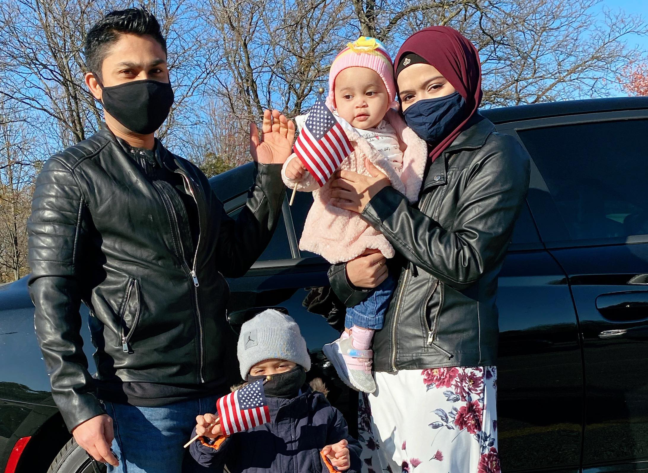 A Rohingya family in Chicago poses in front of their car. The parents wear black leather jackets and are masked. The mom is in a red hijab that matches her flowery dress. The two children wave American flags.