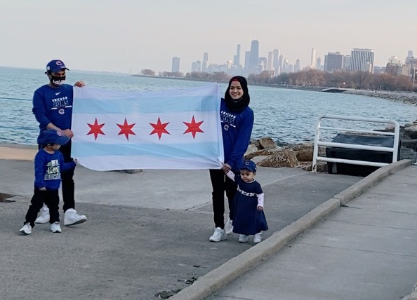 Samad Abdul and his family hold the Chicago flag while posing in front of Lake Michigan and the city skyline. The Rohingya family -- Samad in a ball cap, his wife in a black hijab, and their two American-born toddlers -- are all wearing Cubs gear.