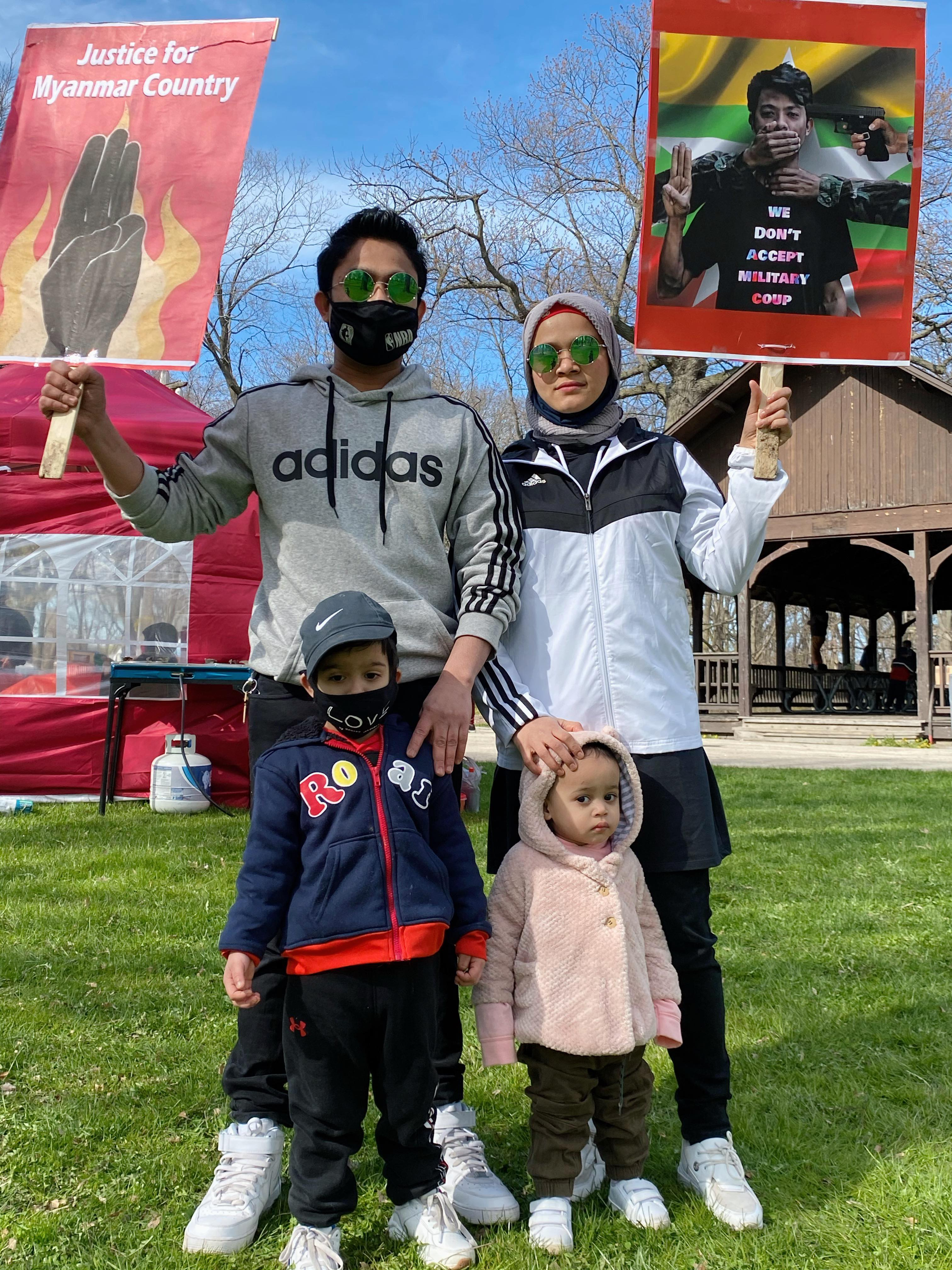 A Rohingya family of four holds signs demanding justice for Myanmar. They are dressed for Chicago spring weather.