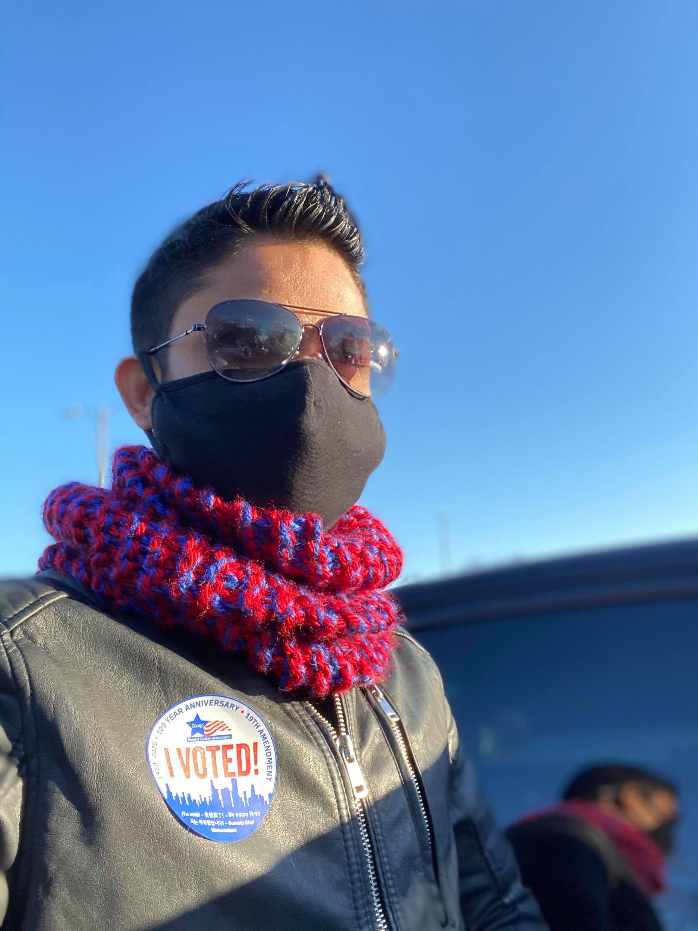 """A Rohingya man in sunglasses, black mask, red and blue scarf, and leather jacket poses with his """"I voted"""" sticker. He is outside on a clear, sunny day."""