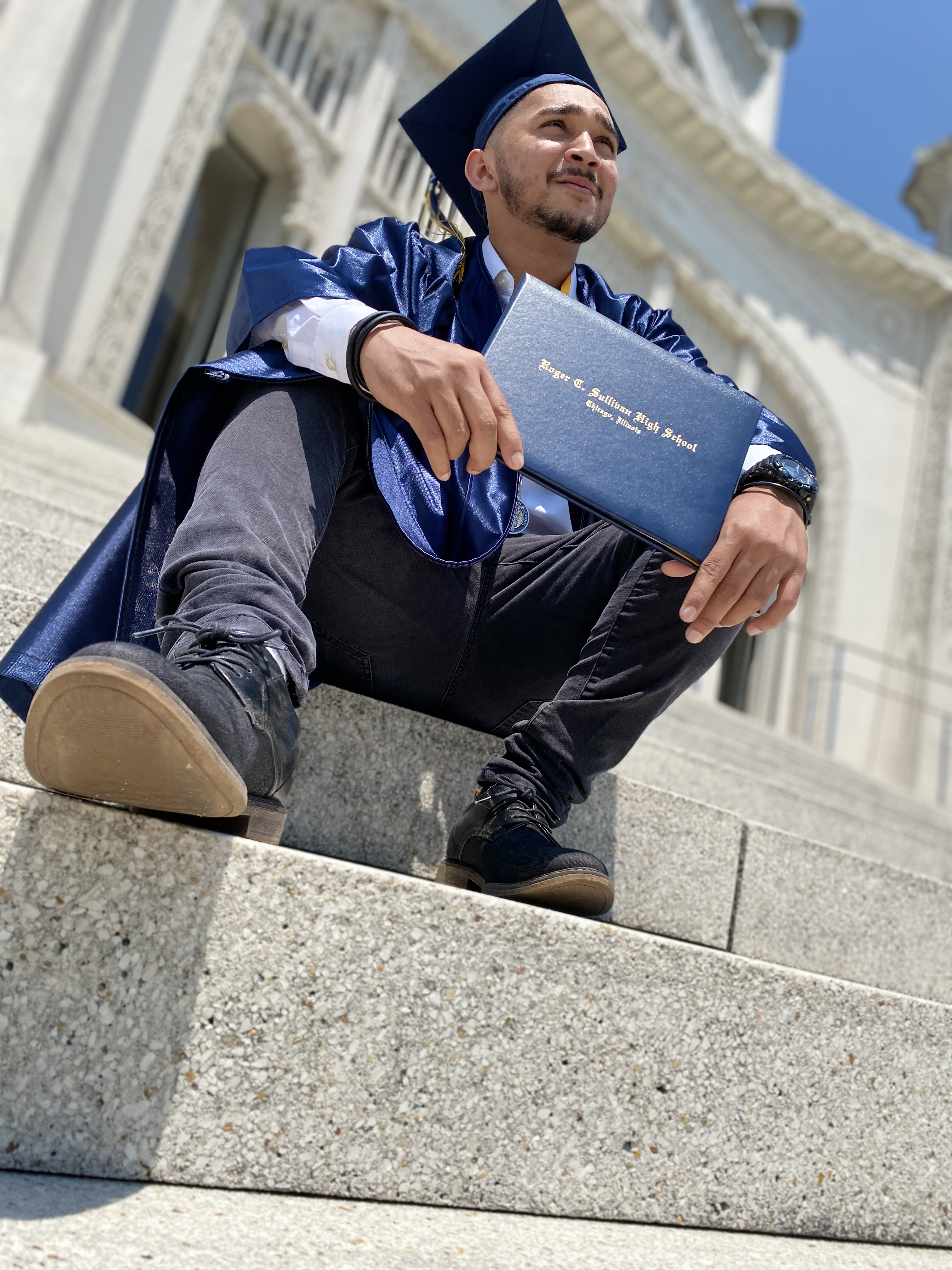 A young man in a blue cap and gown looks into the distance while centering his high school diploma. The photo is taken from a few steps down, increasing the grandeur of his accomplishment through the angle.