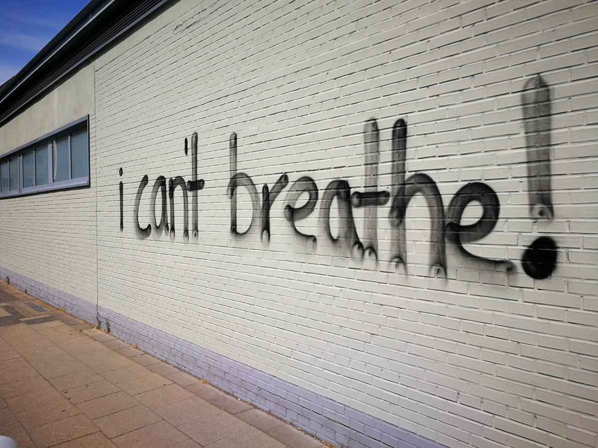"""A white brick wall is spray painted, """"I can't breathe!"""""""
