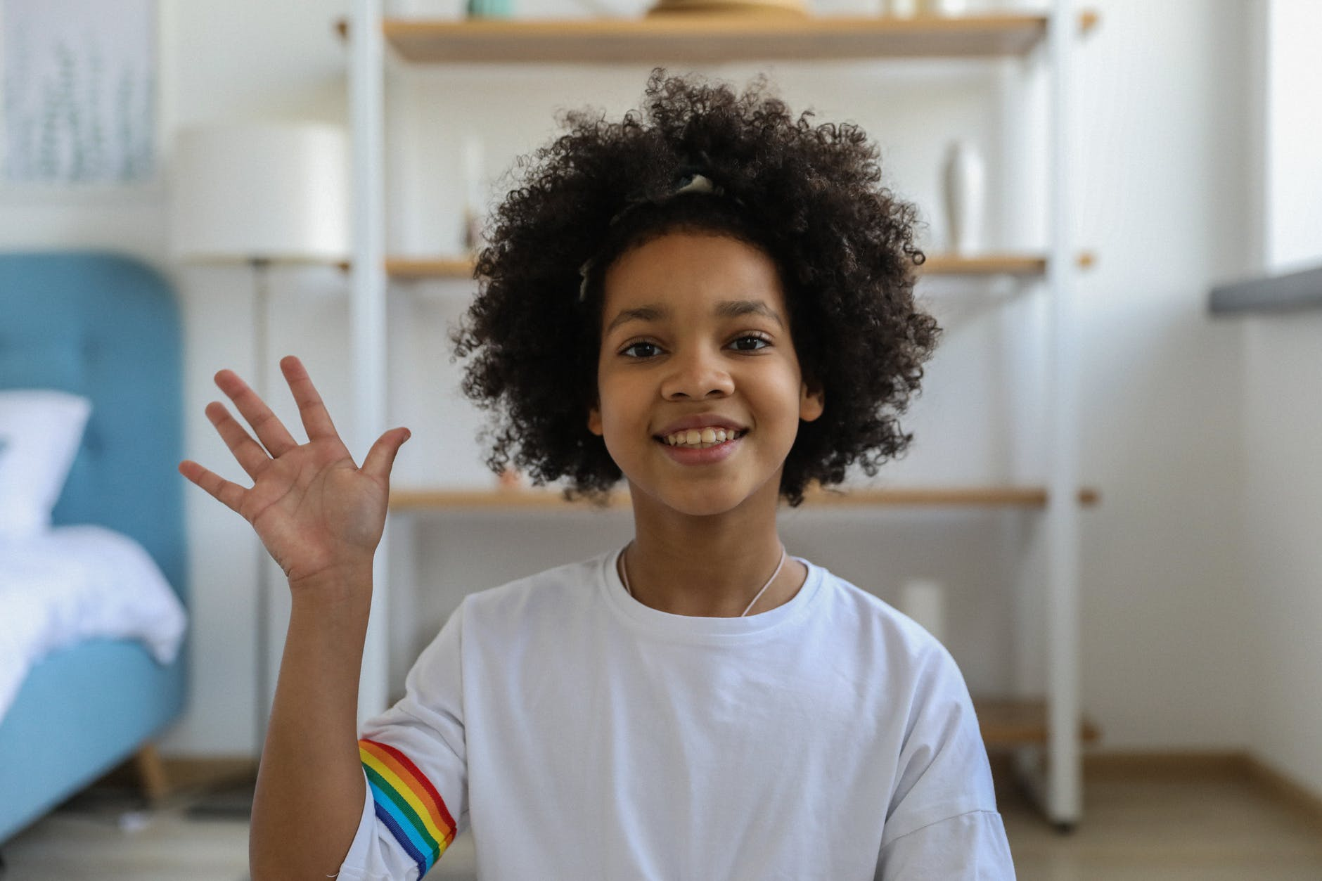 Child sitting in room waving