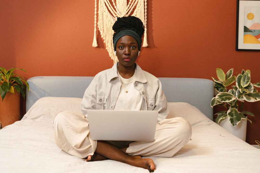 A Nubian queen sits centered on her bed, staring straight into the camera. She is on her laptop. The wall behind her is rust orange, and the rest of the decor is off white.
