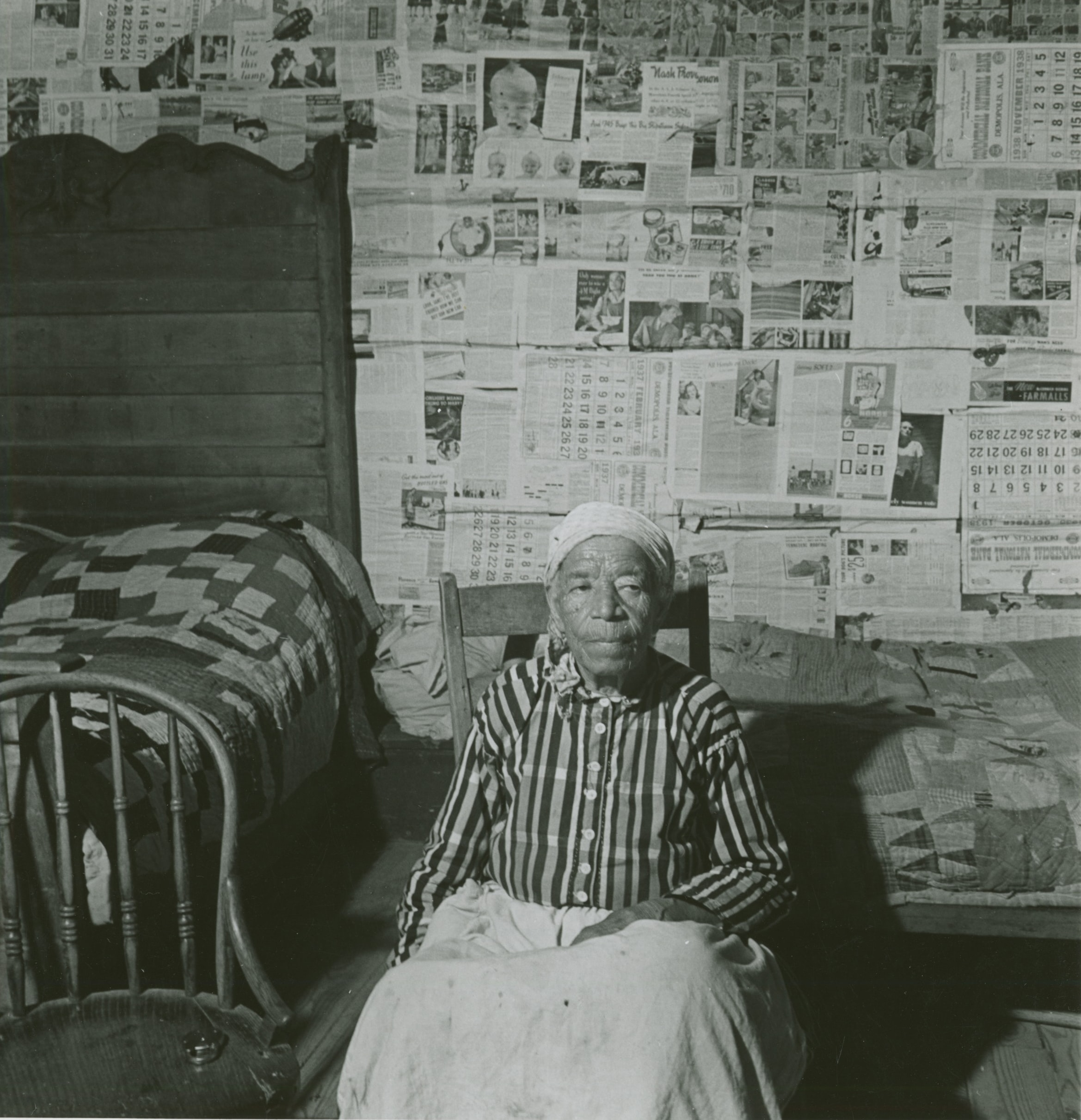 Black and white photo of an elderly mulatto woman in her house. She is sitting, and the wall behind her is lined with newspapers.