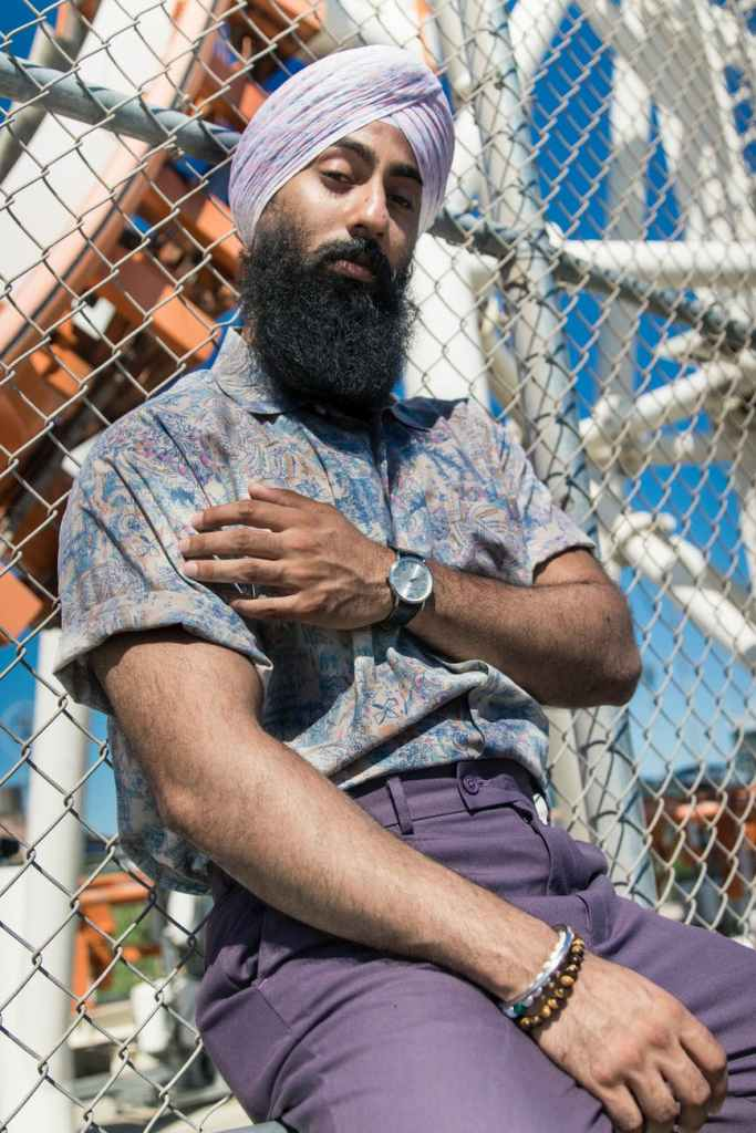 Sikh man wearing mauve pants and a tucked button down with cuffed sleeves.