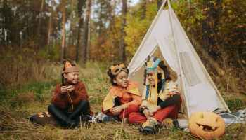 Three young children sit outside in a forested area by a teepee. It is a candid shot, and they are smiling, laughing, and wearing homemade headdresses. A carved pumpkin sits off to the right.
